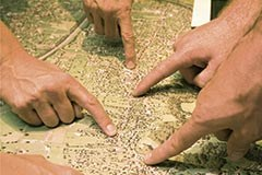 Hands indicating locations on a map