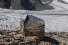 Il rifugio Monte Rosa-Hütte già quasi ultimato: la facciata sud, con la sua inclinazione ottimale, è completamente ricoperta da pannelli fotovoltaici e la struttura in legno è protetta da un involucro di alluminio.